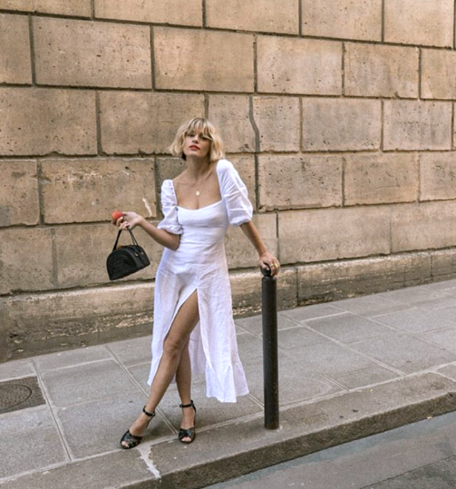 blonde girl wearing white dress with puffed short sleeves, square neckline and leg opening, mini black handbag
