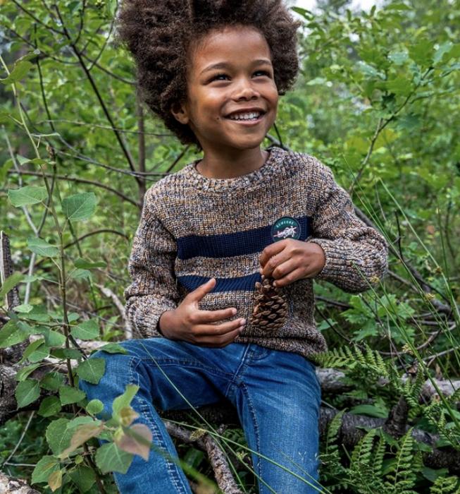 niño de cabello chino usando un suéter café tejido, pantalón de mezclilla azul