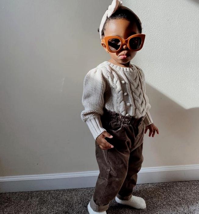 niña bebé morena con lentes de sol, suéter tejido blanco, pantalones cafés, calcetines blancos