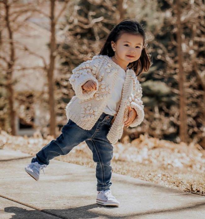 niña de cabello corto usando una camiseta blanca, suéter cárdigan beige, tenis blancos y pantalones de mezclilla