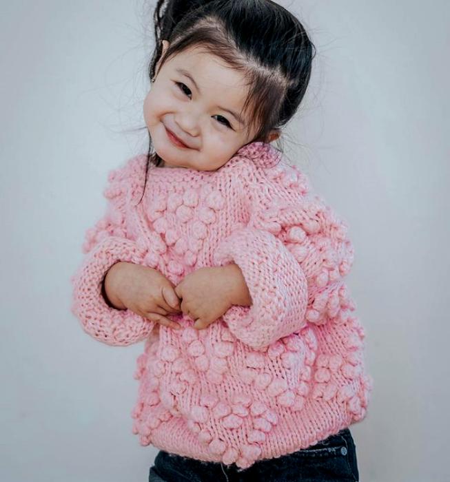 niña de cabello oscuro usando un suéter tejido rosa y shorts de mezclilla
