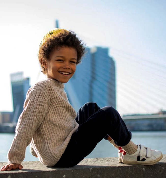 niño de cabello chino usando un suéter gris tejido, pantalones azules, tenis blancos