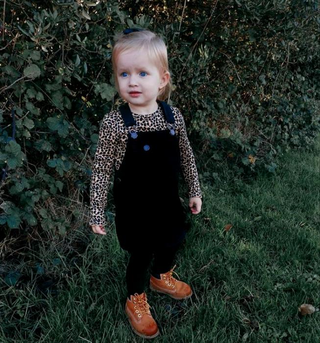 niña rubia de ojos azules usando una blusa de animal print, overol con falda negro, medias negras y botines cafés de piel