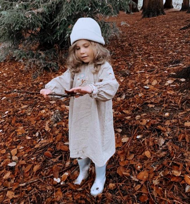 niña rubia usando un sombrero blanco tejido, vestido largo beige de manga larga, botas blancas