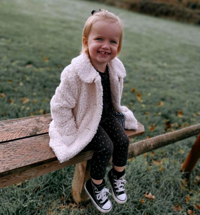 niña de cabello rubio con ojos azules, usando una sudadera negra con lunares blancos, pantalon negro con lunares blancos, tenis converse negros y abrigo teddy color beige