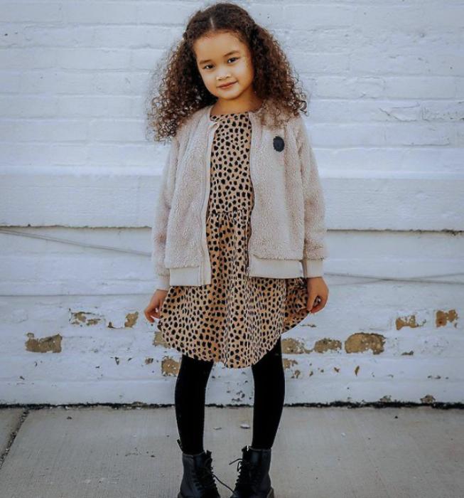 niña de cabello chino castaño usando un vestido café claro, medias negras, botines negros, suéter cárdigan beige