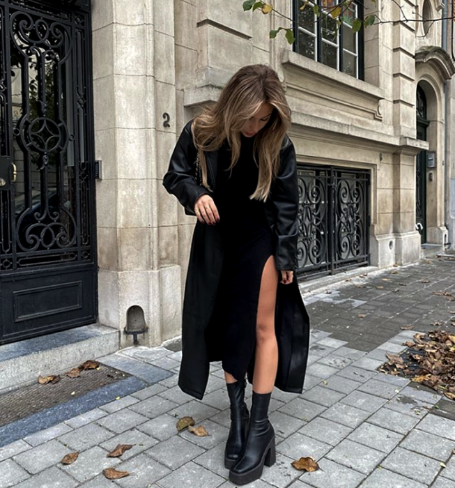blonde girl wearing long leather coat, black knit dress with leg opening, thick soled leather boots and black handbag
