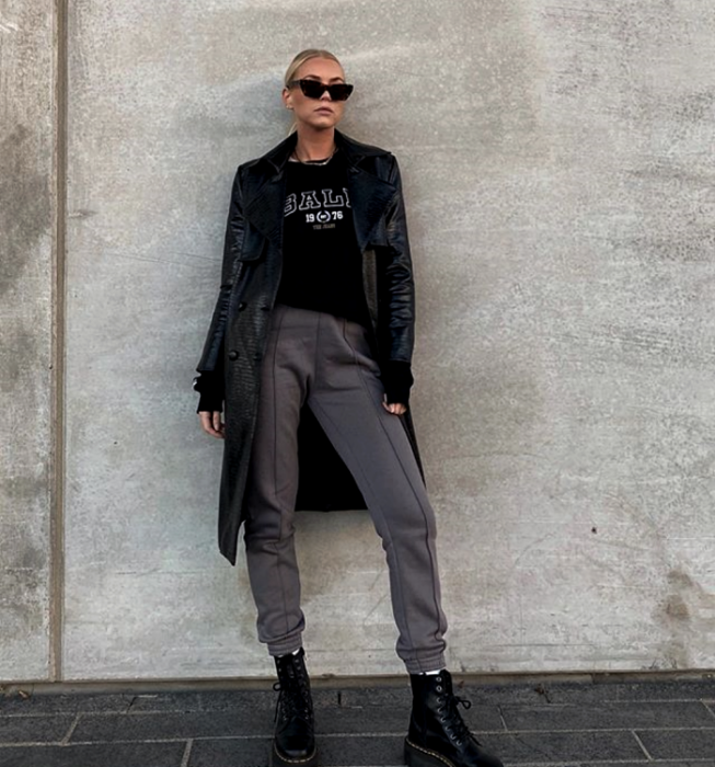 blonde girl wearing sunglasses, black sweatshirt, long black leather coat, gray pants, thick-soled black leather ankle boots