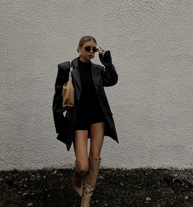 blonde girl wearing sunglasses, black mini dress, long black leather coat, beige leather long boots with heel and beige leather mini handbag