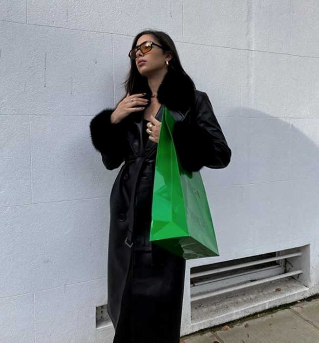 dark haired girl wearing sunglasses, long black leather coat with plush lapels, bright green handbag