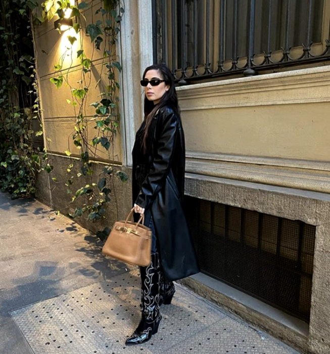 black haired girl wearing sunglasses, long leather coat, long leather boots with heels, beige handbag