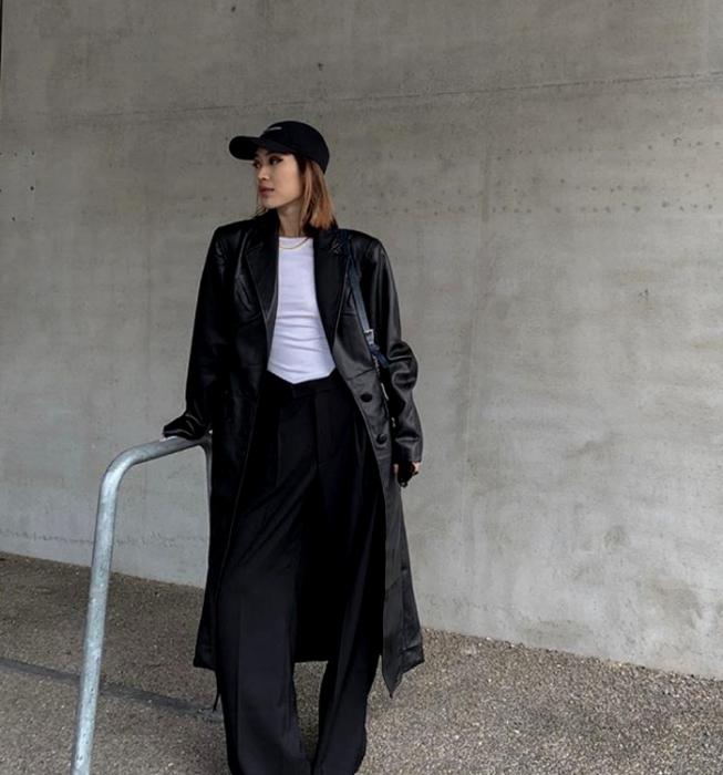 blonde girl wearing a black cap, white t-shirt, long leather coat, black dress pants