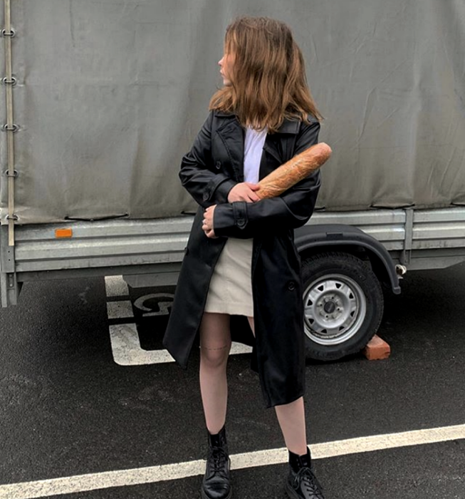 light-haired girl wearing a white t-shirt, beige mini skirt, long leather coat, and black chunky-soled boots