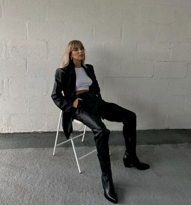 blonde girl wearing a white crop top, long leather coat, black leather pants, heeled leather ankle boots