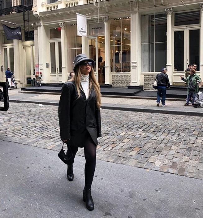 chica rubia con bucket hat gris, top blanco de cuello alto, abrigo de cuero, medias negras semitransparentes, minifalda negra, botines negros de tacón y bolso de mano negro