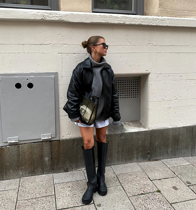 brown-haired girl wearing sunglasses, gray knitted turtleneck sweater, leather jacket, white shorts, long thick-soled leather boots, and semitransparent handbag