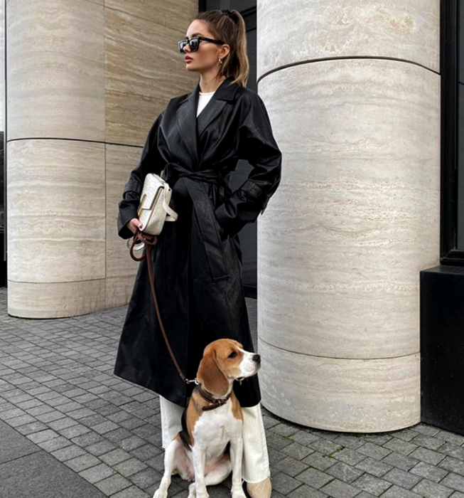 light-haired girl wearing sunglasses, long leather coat, white t-shirt, white dress pants, beige leather boots and white handbag