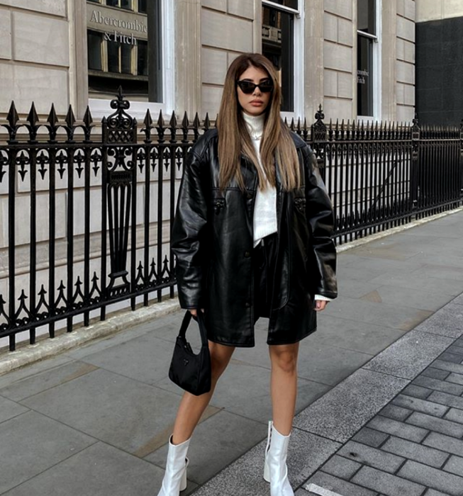 light long hair girl wearing sunglasses, white turtleneck sweater, leather shorts, long leather coat and white high heel ankle boots, black handbag