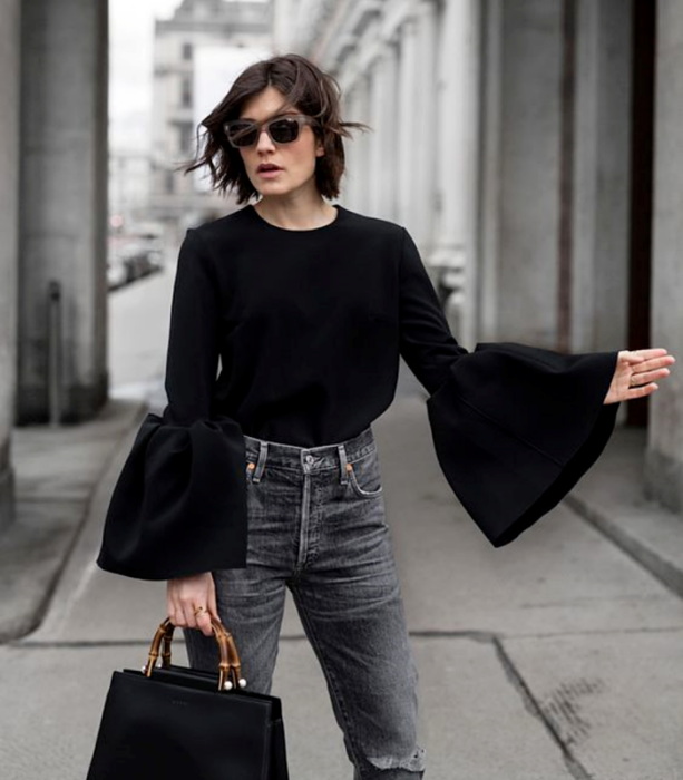 short hair girl wearing sunglasses, black blouse with puff sleeves, waist jeans and black handbag with bamboo strap