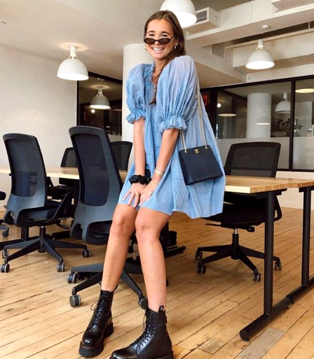girl with light brown hair wearing sunglasses, light blue dress with puff sleeves, blue leather bag, black thick-soled ankle boots