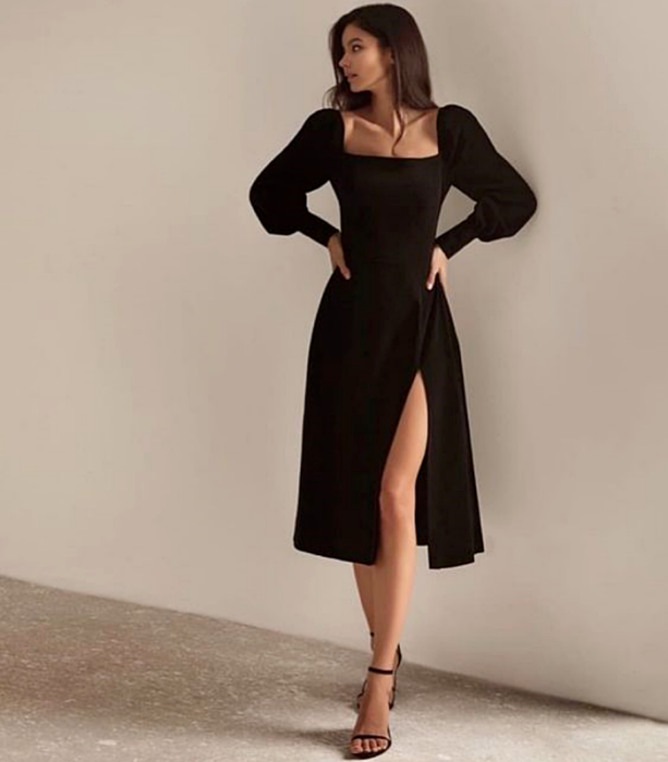long brown hair girl wearing black puff sleeves dress with square neckline and leg opening, black heeled sandals