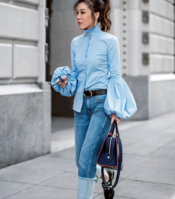 chica de cabello castaño con blusa azul celeste con mangas abombadas y cuello alto, jeans a la cintura, mocasines negros y bolso azul marino de mano