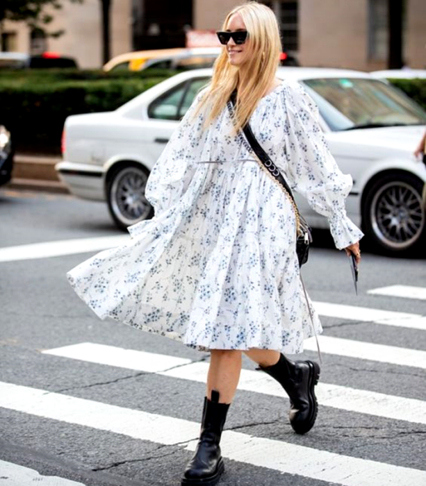blonde girl wearing long white dress with puff sleeves, with small blue flowers, black thick-soled boots and black crossbody bag