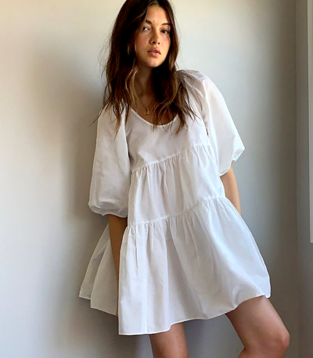 brown haired girl wearing a white dress with puffed short sleeves and round neck