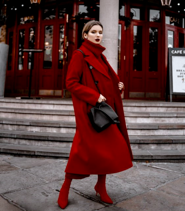brown haired girl wearing red turtleneck sweater, long red coat, red culotte style pants and black high heel ankle boots, black leather crossbody bag