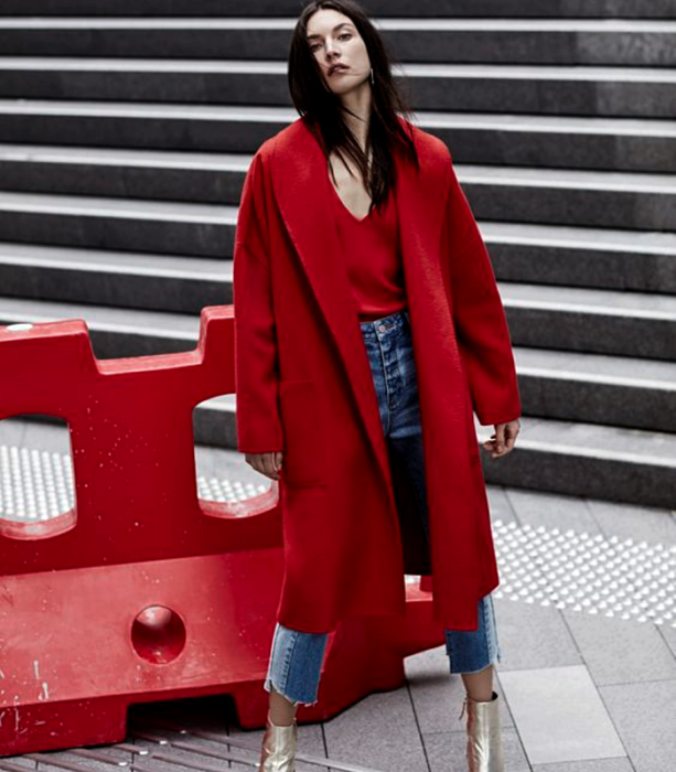 black haired girl wearing red V neck top, long red coat, skinny jeans, gold high heel ankle boots