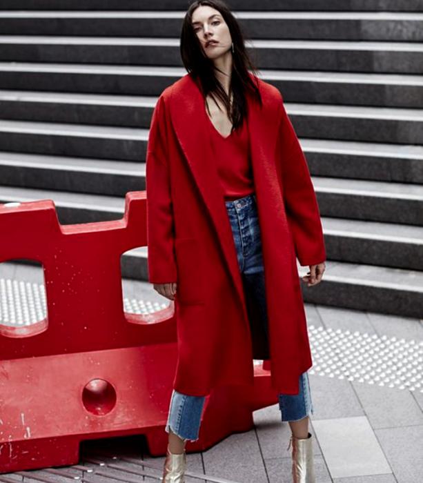chica de cabello negro usando un top rojo de cuello en V, abrigo largo rojo, jeans ajustados, botines dorados de tacón