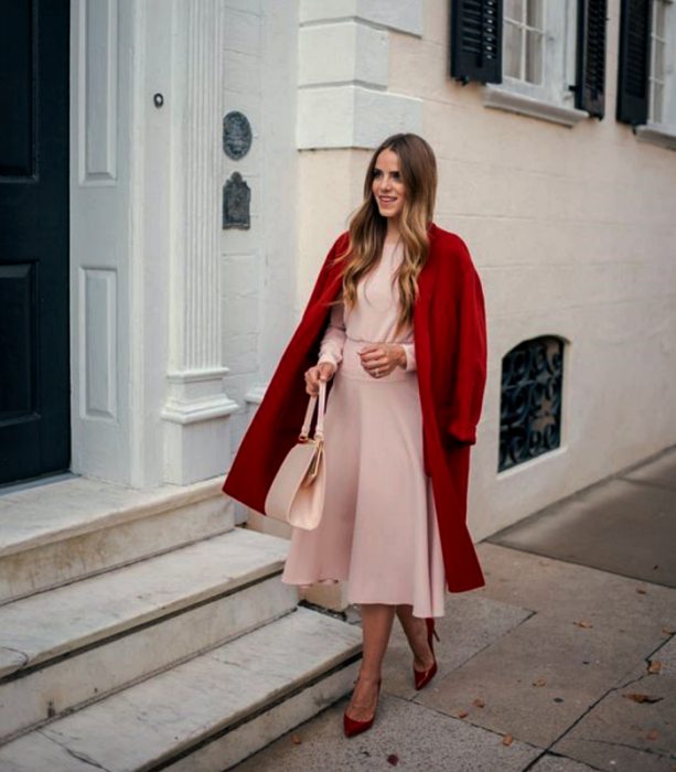 chica rubia usando un vestido rosa largo de manga larga y ajustado a la cintura, abrigo largo rojo, bolso de mano rosa y tacones rojos