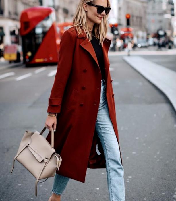 blonde girl wearing long sleeve black top, long red coat, waist jeans, beige handbag