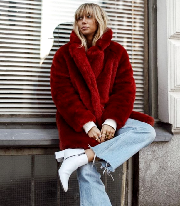 blonde girl wearing a red plush coat, straight baggy jeans, white heeled ankle boots and white long sleeve top
