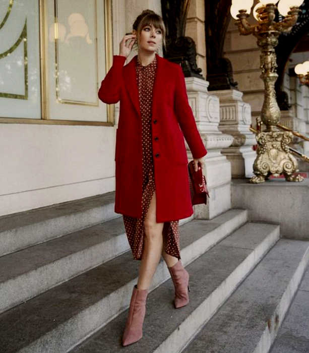 light haired girl wearing red white polka dot dress, long red coat, pink velvet ankle boots and red handbag