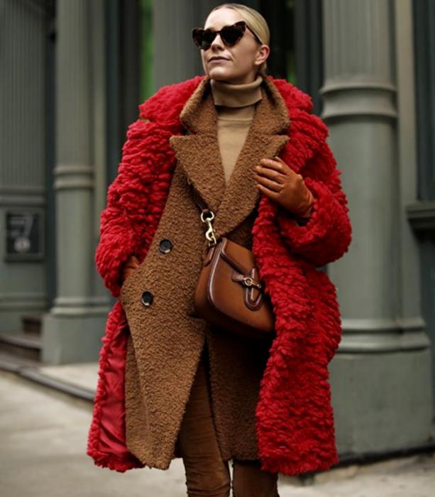 blonde girl wearing sunglasses, beige turtleneck sweater, brown teddy coat, long red plush coat and brown fur bag