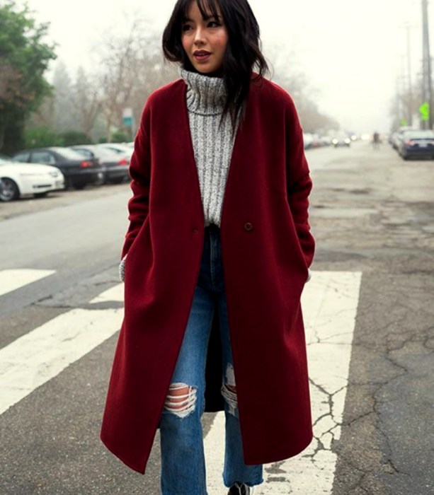 brown haired girl wearing gray turtleneck knitted sweater, long red coat, knee ripped skinny jeans, black heeled ankle boots