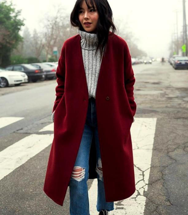 chica de cabello castaño usando un suéter gris tejido de cuello alto, abrigo largo rojo, jeans ajustados rotos de la rodilla, botines negros de tacón
