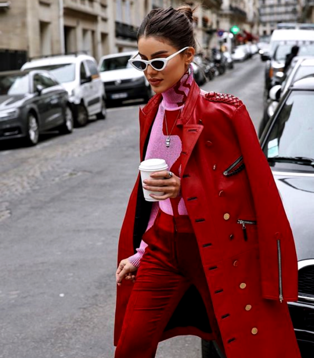 dark haired girl wearing white sunglasses, pink high neck sweater with red print, long red coat, red dress pants