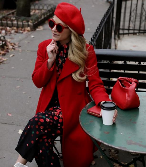 chica rubia usando lentes de sol rojos, beret rojo, vestido negro con flores rojas, abrigo rojo largo y bolso de mano rojo