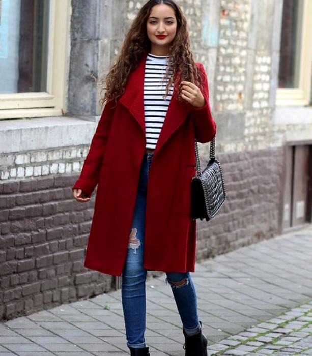 chica de cabello castaño largo usando un top blanco de rayas negras, abrigo largo rojo, skinny jeans, botines negros de piel y bolso de mano  negro