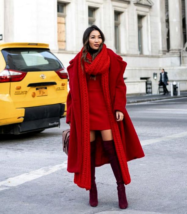 chica de cabello castaño usando una bufanda roja larga, vestido mini rojo, botas largas guindas de terciopelo, abrigo largo rojo y bolso de mano café