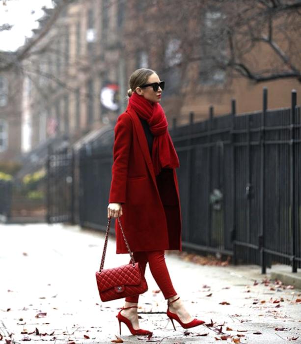 chica de cabello claro usando lentes de sol, bufanda roja gruesa, top rojo, pantalones ajustados rojos, abrigo rojo largo, bolso de mano rojo y zapatos de tacón rojos