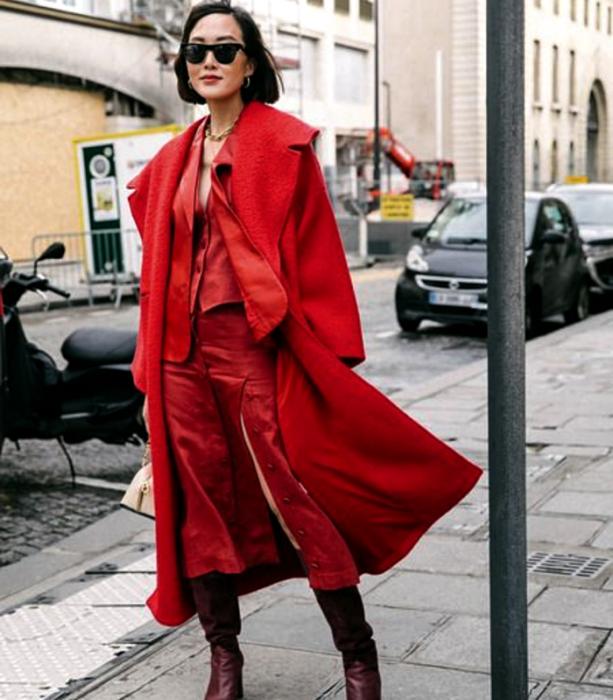 chica de cabello corto usando lentes negros de sol, abrigo largo rojo, top rojo de satén con cuello en V, falda de satén roja con botones al frente y botas largas guindas