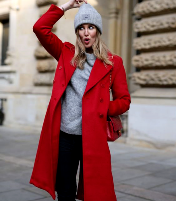 blonde girl wearing gray beanie hat, gray sweater, long red coat, baggy black jeans and red tote bag