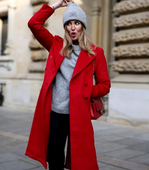 chica rubia usando un gorro beanie gris, suéter gris, abrigo largo rojo, jeans negros holgados y bolso de mano rojo