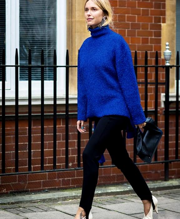 chica rubia usando un suéter azul de cuello alto, leggings negros con estribos, zapatos blancos de tacón y bolso negro de mano