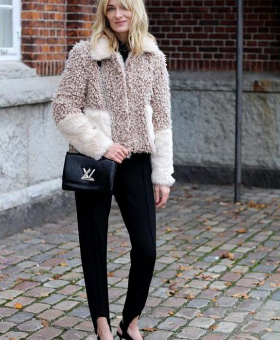 chica rubia usando un abrigo café con beige afelpado, leggings negros con estribos, bolso de mano negro y top negro