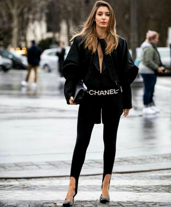 chica de cabello claro usando una blusa negra de mangas abombadas largas, leggings negros con estribos, cinturón de chanel, bolso negro de mano y zapatos negros de tacón con aplicaciones de brillantes en la punta