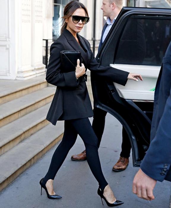victoria beckham usando lentes de sol, blazer negro, leggings negros con estribos, zapatos de tacón y bolso negro de mano